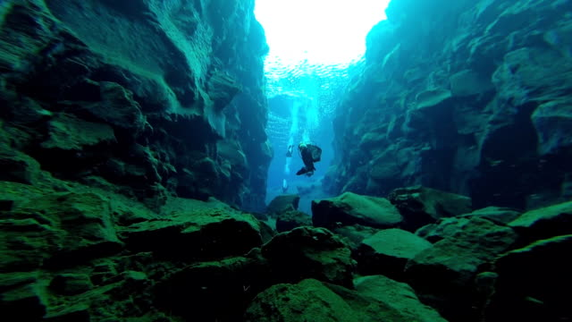 Underwater view of scuba divers approaching and swimming through the 'Cathedral' section of the Silfra Fissure in Iceland's Thingvellir National Park.