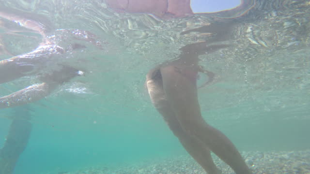 Underwater POV of woman walking then diving into the sea