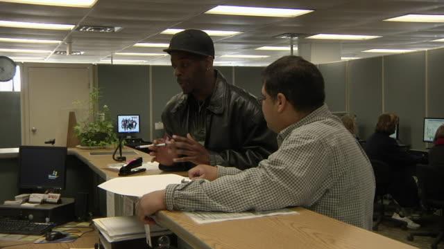 MS Unemployed worker talking to advisor at Michigan Works job center, Jackson, Michigan, USA