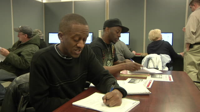 MS ZI CU Unemployed workers filling out paperwork and applications at Michigan Works job center, Jackson, Michigan, USA