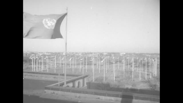 Unformed personnel unfurl flags of different nations in a circular configuration with closeups of UN banner prominently featured / Note exact year...