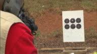 MS Unidentifiable dark skinned male hands firing AR 15 Platform long assault rifle at firing range REFRAMES to barrel of gun discharging rounds...