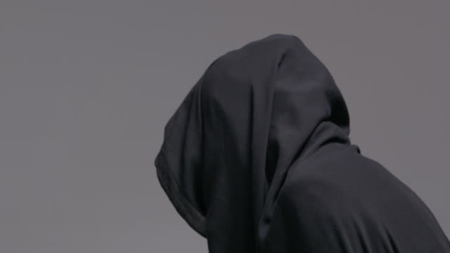 Unidentifiable hooded figure turns around as camera pans in