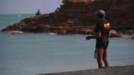 Unidentifiable indigenous Australian male fishing with a hand line off rich red coloured rocks against the aqua sea Australian Aboriginal colours on...