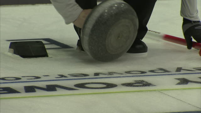 Unidentifiable male aka the skip standing in house area of ice curling sheet wiping bottom of curling stone spinning stone launching off hack...