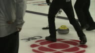 Unidentifiable male curlers following sliding curling stone on ice curling sheet sweeping stone hitting other team's stone in house legs kicking amp...