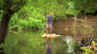 Unidentifiable male in shorts standing on raft using pole to push forward in flooded standing water area