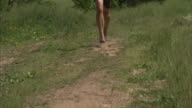 Unidentifiable male legs jogging wearing five finger foot glove on dirt road in unidentifiable rural countryside area Jogger jog runner barefoot...