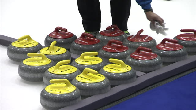 Unidentifiable male wiping curling stones lined up w/ other curling stones on edge of ice curling sheet Sports