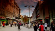 Unidentifiable people walking on crowded Cardiff city centre street in market or shopping area UK