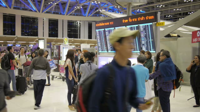 Unidentified air passengers walk by and stop at a departures timetable in the Suvarnabhumi International Airport
