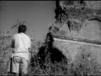 Unidentified boy playing harmonica near ruins standing up walking away MS TRACKING Boy walking by tall vegetation TU WS Crumbling wall sections BG