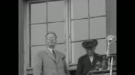Unidentified man and woman stand on balcony with radio microphone 'NWDR' man is emotionally moved by the crowd he sees / large crowd of subdued...