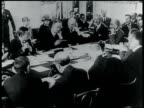 Unidentified men in suits talking at table peace conference World War I