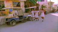 Uniformed school girls walk along pavement whilst looking into camera, Belize Available in HD.