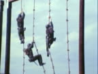 WS Uniformed US Marines climbing down a knotted rope during training session / California, Untied States