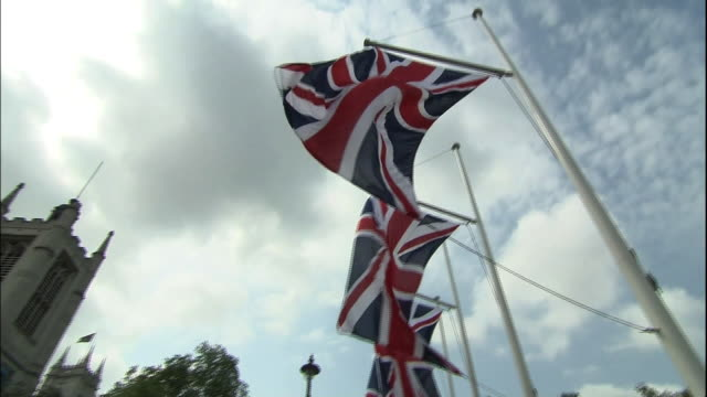 Union Flags wave near Westminster Abbey in London, England.