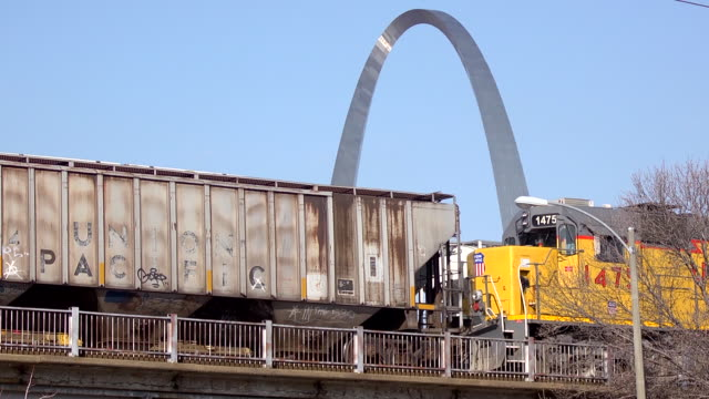 Union Pacific and graffitiladen freight trains moving along elevated railroad tracks in both directions w/ Gateway Arch in BG