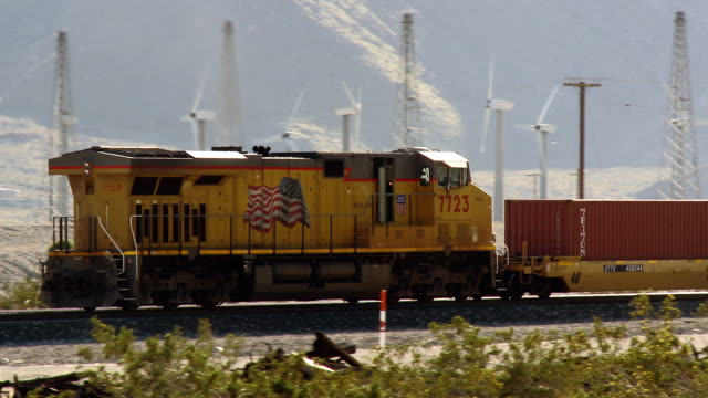 A Union Pacific locomotive pushes freight cars loaded with double stacked shipping containers through the California desert.