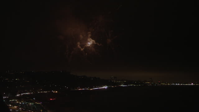 A unique pattern of fireworks bursts over Santa Monica Bay, with Santa Monica city lights in the background.