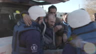 United Nations and Syrian Arab Red Crescent aid workers helping injured refugees evacuate Homs February 15 2014