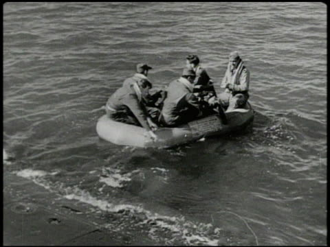 United States Air Force crew boarding lifeboat raft paddling out to sea World War II WWII lost at sea rescue craft