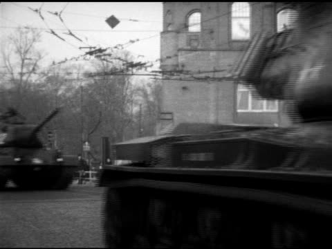 United States Army tanks rolling through West Berlin town soldiers manning turrets atop tanks tanks tank trucks rolling through American Sector...