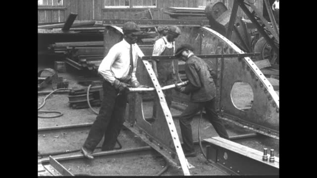 United States champion riveter Charles Knight works on ship / shipbuilding / workers in shipyard