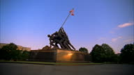 WS United States Marine Corps War Memorial w/ sunlight reflecting off base Military statue soldiers erecting American flag Mount Suribachi WWII World...