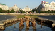 WS Unity Square Fountain in Piata Unirii with Palace of Parliament in background / Bucharest, Romania