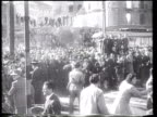 Benito Mussolini and his mistress Clara Petacci are executed displayed and hung by vengeful Italians in Milan