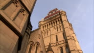 A University of Manchester sign hangs over the University's arched doorway Available in HD.