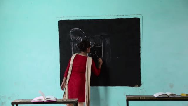 University student writing on the blackboard, Haryana, India