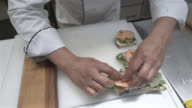 Unrecognisable chef preparing appetisers with smoked salmon and vegetables on a toast