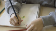 Unrecognisable child at school painting in his notebook