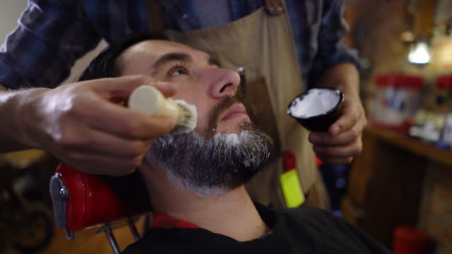 Unrecognizable barber putting shaving cream on the customers face