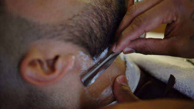 Unrecognizable barber shaving a customer with a classic razor
