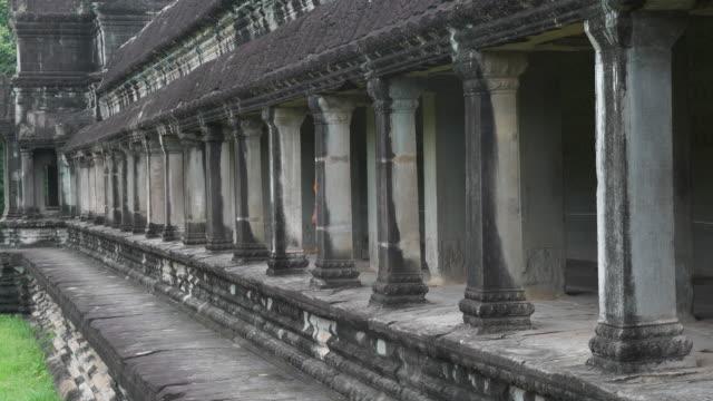 Unrecognizable Buddhist Monk Walking Past Temple Pillars