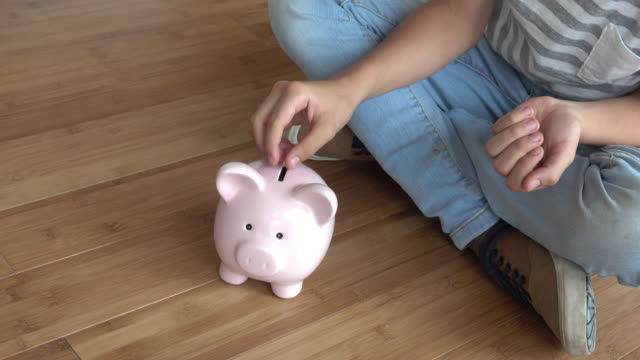 Unrecognizable child putting coins into a piggybank