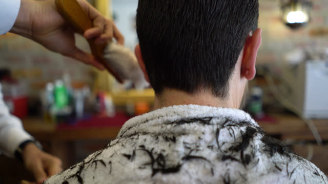 Unrecognizable customer cleaning the customers neck after a hair cut