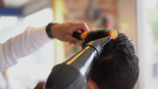 Unrecognizable hairdresser drying the hair of an unrecognizable customer