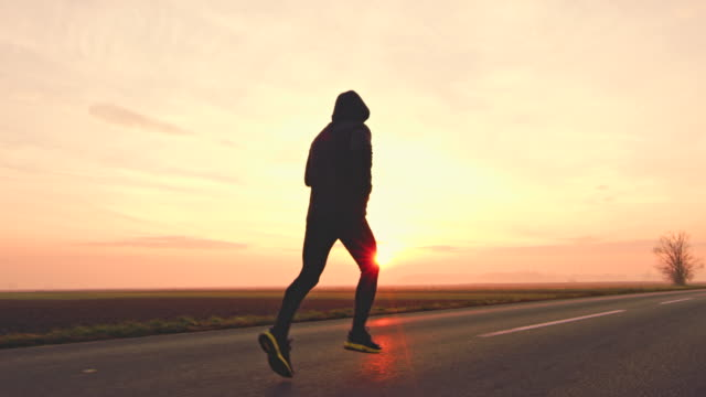 WS Unrecognizable man jogging on a country road