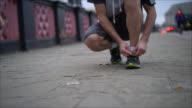 Unrecognizable man tying his tennis shoe  to start running