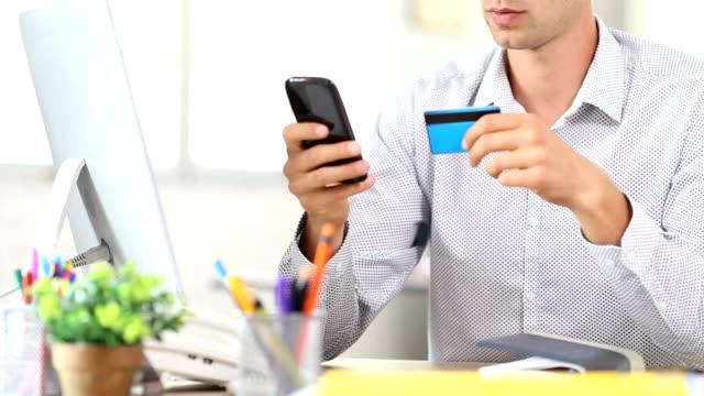 HD unkenntlich Mann mit Smartphone und Kreditkarte für kontaktloses Bezahlen