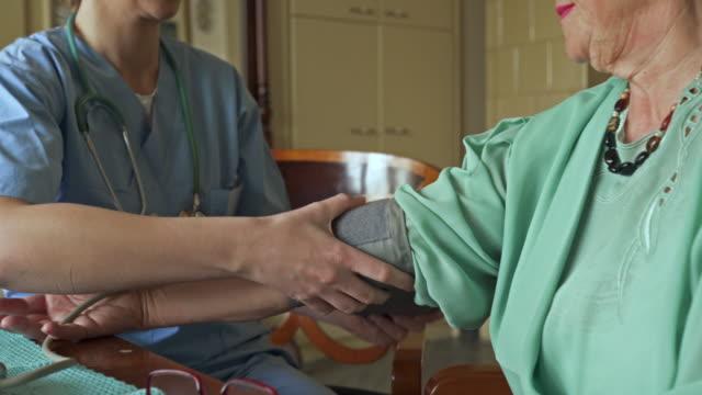 Onherkenbare oude vrouw krijgt haar bloeddruk gemeten door vrouwelijke verpleegkundige.
