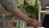 CU, Unrecognizable person arranging flowers and candlesticks on table, close-up of hands