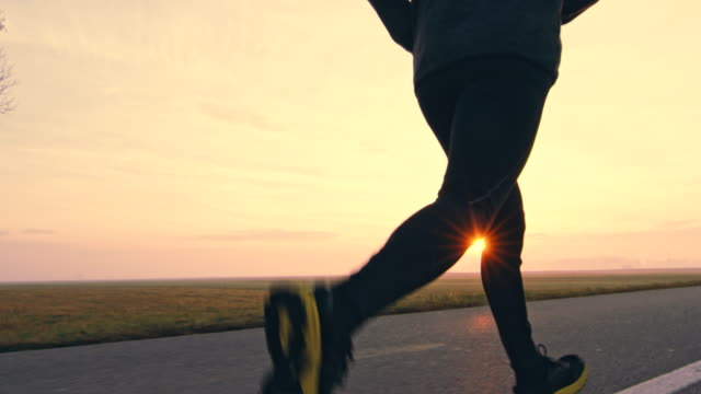 MS Unrecognizable person jogging on a country road