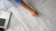 Unrecognizable person looking at blueprints and taking notes on laptop