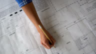 Unrecognizable person working on blueprints