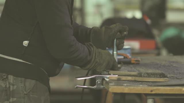 Nicht erkennbare Stahlarbeiter Bürsten Metallteil mit Eisen Pinsel in einer Reparaturwerkstatt.